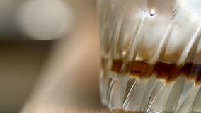 Closeup view empty misted cold glass with dark brown whiskey drink.  Royalty Free Stock Photography