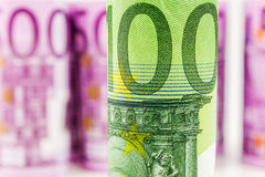 Closeup view of 100 euro rolled banknote. With the background made of 500 euro banknotes blurred and rolled up Royalty Free Stock Images
