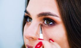 Closeup female hands applying eyeshadows on cute young woman`s eyelids using special brush royalty free stock photography