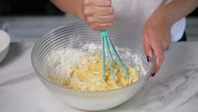 Closeup view of female hands mixing sticky dough in the kitchen using whisk. Homemade food. Slowmotion shot stock video footage
