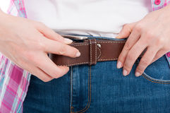 Closeup view on female jeans with leather belt stock image