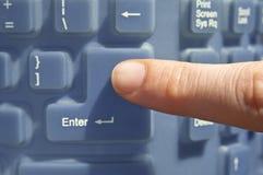 Finger pressing a computer keyboard key. Stock Photos