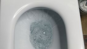 Toilet, Flushing Water, close up. Closeup view of a flushing white toilet. The water swirls in the toilet bowl stock footage