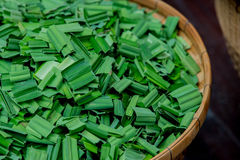 A closeup view focusing on the in knot pandan leaves leaving the long leaves underneath the bamboo plate Royalty Free Stock Photo