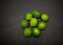 closeup view of fresh appetizing green limes on dark grey background Royalty Free Stock Photo