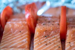 Closeup view fresh raw salmon fillets with herbs and spices on baking tray ready to be cooked in oven.  Royalty Free Stock Photo