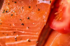 Closeup view fresh raw salmon fillets with herbs and spices on baking tray ready to be cooked in oven.  Stock Image