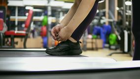 Closeup view of girl`s hands tying shoelaces on her sneakers which are standing on the treadmill in the gym. Shot in 4k stock footage