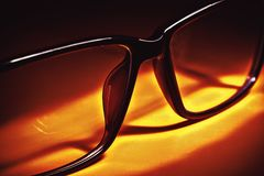 Glasses on Table. Closeup view of glasses for eyesight in orange atmosphere royalty free stock image