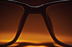 Glasses on Table. Closeup view of glasses for eyesight in orange atmosphere royalty free stock photo