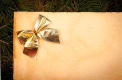 Closeup view of golden bow on old paper Royalty Free Stock Image