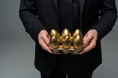 Closeup view of golden eggs in hands of male royalty free stock images