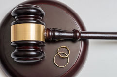 Closeup view on golden rings and gavel in background. Divorce concept royalty free stock photo