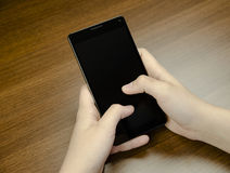 Closeup view of a hand with fingers holding a black cell phone with black screen on wooden mat Stock Images