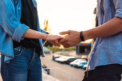 Lovely young hipster couple dating during summer sunset. Closeup view of hands of lovely young couple dating during summer sunset. they wear jeans clothes royalty free stock photography