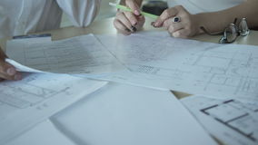 Closeup view on hands of office workers and documents indoors. United team of architects working on common building project with couple of floors. Actively stock video footage