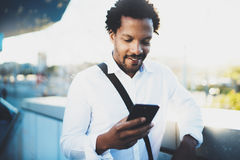 Closeup view of Happy smiling African man using smartphone outdoor.Portrait of young black cheerful man texting a sms Stock Image