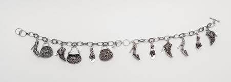 Closeup view of isolated charming silver bracelet with miniature pendants Stock Image