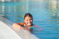 Closeup view of joyful happy little girl swimming in water pool Stock Image