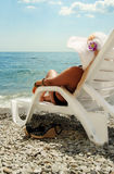 Closeup view on lady in chaise-longue Stock Images