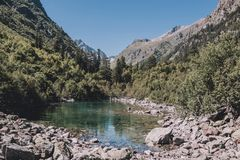 Closeup view of lake scenes in mountains, national park Dombay, Caucasus. Russia, Europe. Sunshine weather, blue color sky, far away green trees. Colorful royalty free stock photo