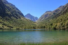 Closeup view of lake scenes in mountains, national park Dombay, Caucasus. Russia, Europe. Sunshine weather, blue color sky, far away green trees. Colorful stock photography
