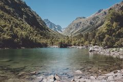 Closeup view of lake scenes in mountains, national park Dombay, Caucasus. Russia, Europe. Sunshine weather, blue color sky, far away green trees. Colorful stock images