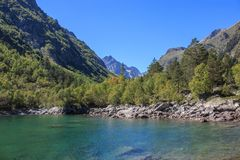 Closeup view of lake scenes in mountains, national park Dombay, Caucasus. Russia, Europe. Sunshine weather, blue color sky, far away green trees. Colorful royalty free stock image