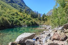 Closeup view of lake scenes in mountains, national park Dombay, Caucasus. Russia, Europe. Sunshine weather, blue color sky, far away green trees. Colorful stock photo
