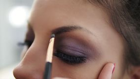 Closeup view of the makeup artist`s hands correcting eyebrows using special brush. Slowmotion shot.  stock video footage