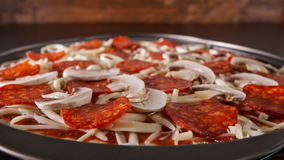 Closeup view of making a pizza with ingredients appearing on the baking plate stock video