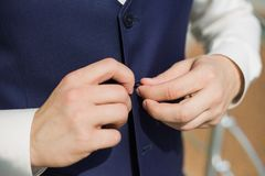 Male hands buttoning vest of blue suit Stock Photos