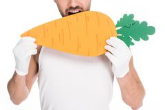 Closeup view of man bitting big carrot isolated on white, easter concept stock images