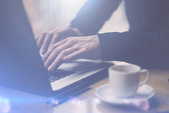 Closeup view of Man in black shirt working with laptop at sunny office.Modern notebook, cup of black coffee and Royalty Free Stock Photo