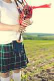 Closeup view of man enjoying playing pipes in traditional style. Green outdoors summer field background Stock Images