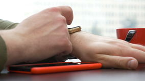 Closeup view of man having a red smartphone using a smart watch in a coffeshop stock video footage