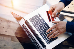 Closeup view of Man holding credit card in hand and typing laptop keyboard while sitting at the wooden table.Reflections Royalty Free Stock Images