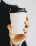 Closeup view of man holding white paper coffee cup to take away.Mock up of carton coffee cup for go outside.Vertical Royalty Free Stock Photos