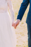 Closeup view of married bride and groom holding hands together Stock Photography