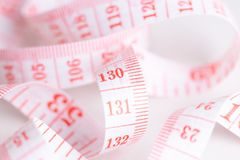 Closeup view of measuring tape on white paper background Stock Photos