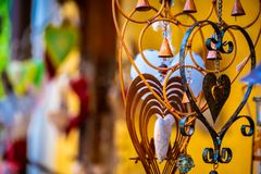 Closeup view of metal jewerly hearts with bells. On the blurred background royalty free stock photo