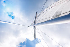 Closeup View of Mid-Size Yacht Mast and Canvas Sail Shot Against Stock Photos
