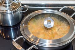 Closeup view misted up pan lid cooking on modern electric cooker.  Stock Images