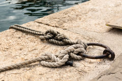 Closeup view of mooring ring and rope tied on it in port of old croatian town Vrsar. stock photography