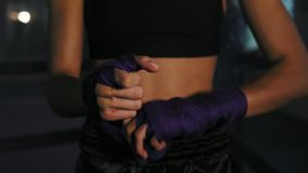 Closeup view of muay thai female boxer wrapping bandages on her hands before fight in dark room with smoke. Shot in 4k.  stock footage