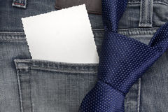 Closeup view of a necktie on jeans trousers. Royalty Free Stock Images