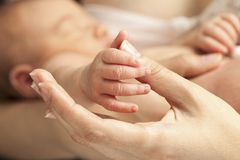 Closeup view of newborn's hand holding mother's thumb Royalty Free Stock Photos