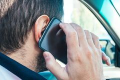 Free Closeup View Of A Man Holding A Mobile Phone Near His Ear And Talking On It While Driving. Danger Of Using The Phone In A Car Royalty Free Stock Image - 161281026