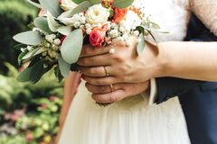 Free Closeup View Of Newlyweds Hands Holding Colorful Wedding Bouquet. Bride And Groom Wearing Wedding Rings. Outdoor Royalty Free Stock Images - 191306729