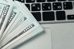 Closeup view of one hundred dollar banknotes lying on the laptop keyboard stock photography